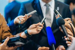 引用画像_記者会見の囲み取材に応じる男性